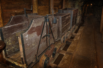 Old wooden mine train with rusty wheels in mine tunnel with wooden timbering