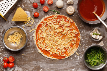 Unbaked pizza with grated cheese and with ingredients around