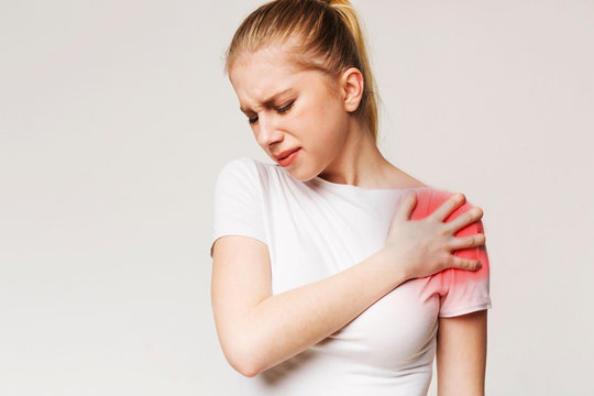 Young woman suffering from pain in shoulder