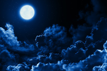 Mystical bright full moon in the midnight sky with stars surrounded by dramatic clouds. Dark natural background with twilight night sky with moon and clouds