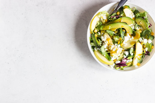 Mix salad with corn, apple, avocado and fresh farm cottage cheese. Healthy and diet food concept. Light concrete background. Copy space.