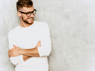 Portrait of handsome smiling hipster lumbersexual businessman model wearing casual summer white clothes and spectacles. Fashion stylish man posing against gray wall