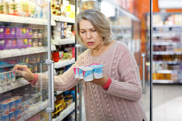 Shocked elderly woman reading product label
