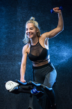 Cheerful sporty woman holding up weight and riding exercise bike during cycling workout indoors