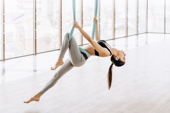 Young pretty slim body fitness girl practicing fly yoga in the gym.