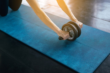 Foto op Textielframe School de yoga Sporty asian female doing workout and exercise with roller wheel on yaga mat,Close up