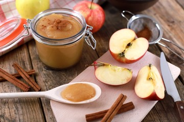 fresh homemade apple jam , apple puree, with cinnamon, fresh apples and a wooden spoon on wooden rustic table