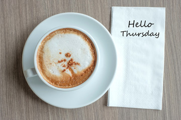 Hello Wednesday text on paper with hot cappuccino coffee cup on table background at the morning