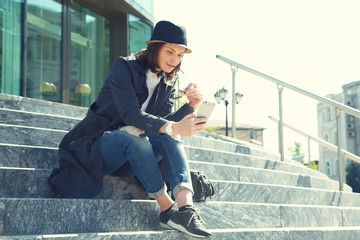 portrait of a stylish woman in hat and sunglasses with smartphone