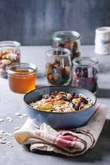 Variety of dried fruits, nuts, honey and oat flakes in bowl and different glass jars for cooking homemade healthy breakfast muesli or granola energy bars on grey blue table.