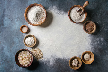 Ingredients for baking bread. Variety of wheat and rye flour, grains, yeast, sourdough and sifted flour over dark blue texture background. Flat lay, space