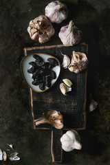 Variety of fresh organic garlic bulbs whole and peeled and cloves of black fermented garlic on wooden chopping board over dark metal background. Flat lay, space
