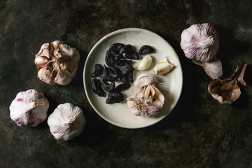 Variety of fresh organic garlic bulbs whole and peeled and cloves of black fermented garlic on ceramic plate over dark metal background. Flat lay, space