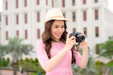 Outdoor summer smiling lifestyle portrait of pretty young woman having fun in the city in Asian with camera travel photo of photographer