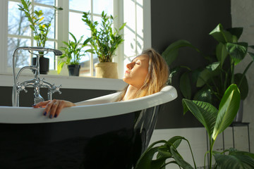 side view of beautiful relaxed woman lying in luxurious bathtub, closed eyes, lots of light, green plants, Scandinavian interior, big windows, sunny weather