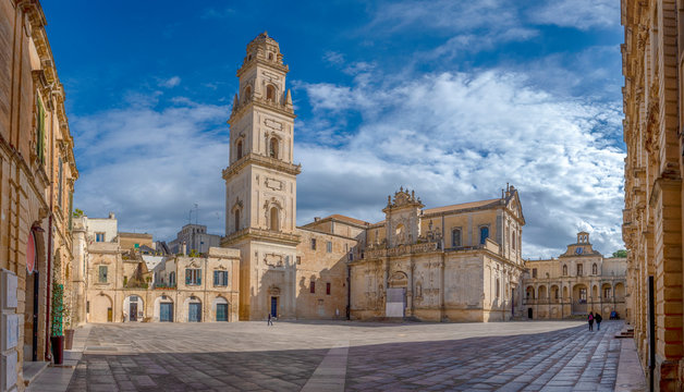 Panorama of Piazza del Duomo square , Campanile tower and Virgin Mary Cathedral ( Basilica di Santa Maria Assunta in Cielo ) , Caritas Diocesana in Lecce - Puglia, Italy. Baroque city of Apulia