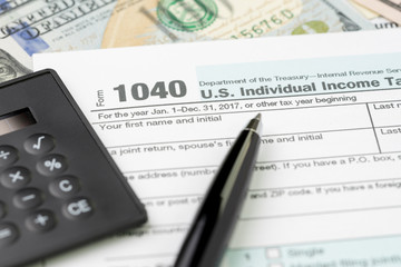 Pen on 1040 US individual income tax filling form with black calculator and US dollar bill, tax submission or revenue calculation concept