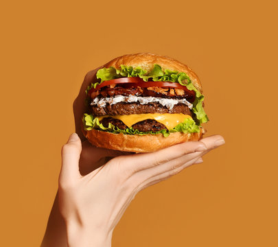 Woman hands hold big double cheeseburger burger sandwich with beef and bacon on yellow
