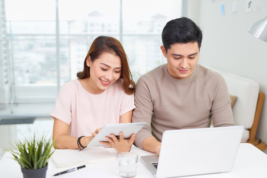 Beautiful young business woman and handsome businessman in formal suits are using gadgets, talking and smiling while working in office
