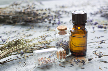 lavender essential oil with lavender on wooden background