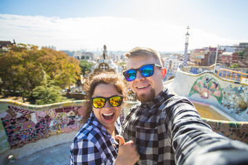 Funny young couple looking at camera taking photo with smart phone smiling in Park Guell, Barcelona, Spain.