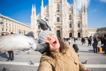 Winter travel, vacations and birds concept - Young happy woman tourist with funny pigeons making selfie photo in front of the famous Duomo cathedral in Milan.
