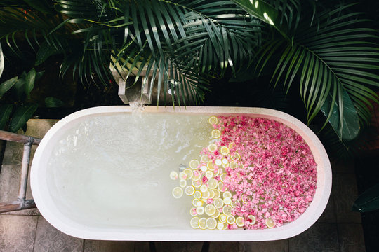 Bath tub filling with water with flowers and lemon slices