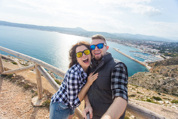 Travel, vacation and holiday concept - Nice couple taking selfie near a sea