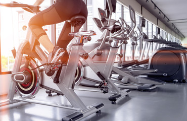 Exercise bike cardio workout at fitness gym of woman taking weight loss with machine aerobic for slim and firm healthy in the morning.