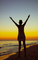 healthy tourist woman on ocean coast at sunset rejoicing