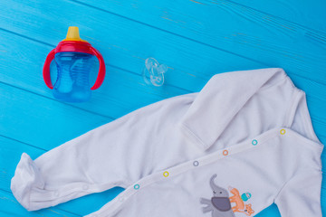 Baby essentials, white wool pajama, bottle and pacifier.