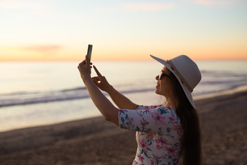 Traveler young woman is shooting video of beautiful sunset landscape on mobile phone camera. Summer vacation travel and holiday.
