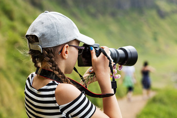 12 year old girl taking pictures with a long lens in a beautiful scenic of Irish cliffs