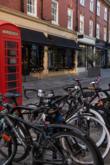 Bicycle parking on the street of London next to the phone booth
