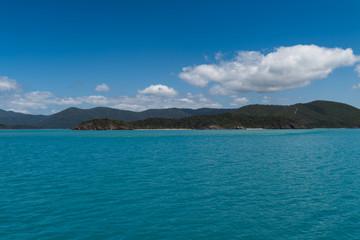 Inselblick in türkis-farbenem Wasser und blauem Himmel mit weißen Wolken