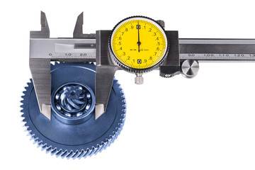 Measurement of cogwheel diameter by caliper. Isolated on white background. Silvery measuring tool. Round yellow dial. Black pointer. Gear wheel and ball bearing check. Blue metal part. Quality control