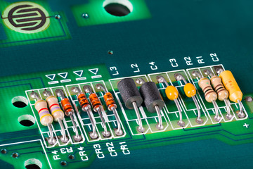 Inductors, capacitors, resistors and diodes on PCB. Close-up of colorful electronic components on green circuit board with holes. Button switch. Disassembled computer keyboard. Electrical engineering.
