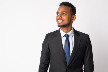 Happy young handsome African businessman in suit thinking