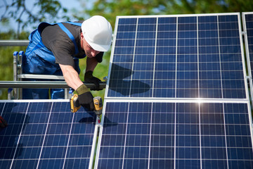 Professional technician standing on ladder connecting solar panel to metal platform using screwdriver. Exterior solar system installation, renewable green energy generation concept.