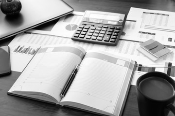 Open leather notebook, laptop, cup of coffee, calculator, graphs, data and drawings on the working office desk. Business and Finance.
