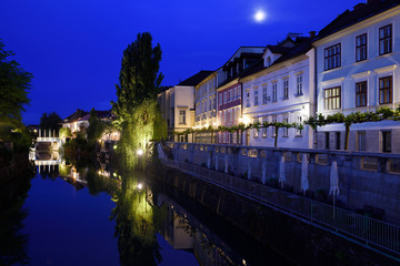 Cobblers Bridge and houses reflected on the calm Ljubljanica river canal in moonlight at dawn in Ljubljana Slovenia