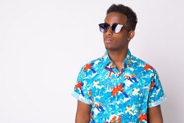 Young African tourist man with Afro hair thinking with sunglasses