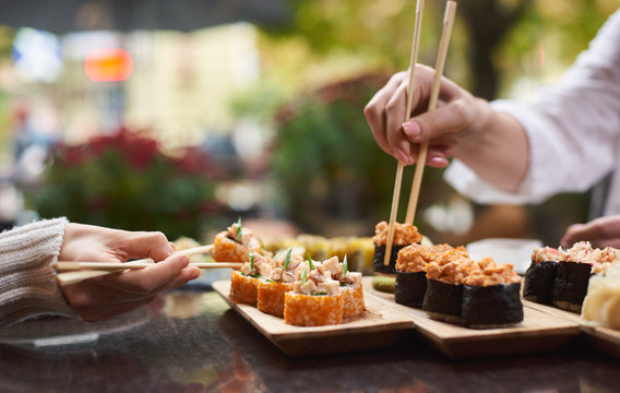 Two women sitting in asian restaurant and eating sushi set with help of chopsticks. Colleagues sharing tasty Japanese dinner with each other. Sisters enjoying oriental meal from rice and seafood.