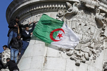 A protestor holds an Algerian flag as people attend a demonstration against President Abdelaziz Bouteflika on the Place de la Republique, in Paris