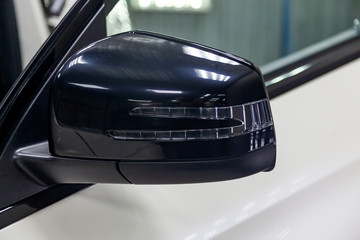 Close-up of the black side mirror of the car body in the design of a white suv with turn light