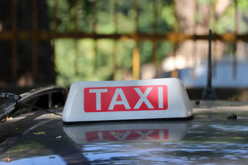 Taxi light sign or cab sign in white and red color with white text on the car roof at blurred background