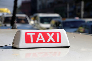 Taxi light sign or cab sign in white and red color with white text on the car roof at the street blurred background