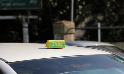 Taxi light sign or cab sign in drab green color with yellow text on the car roof at the street blurred background