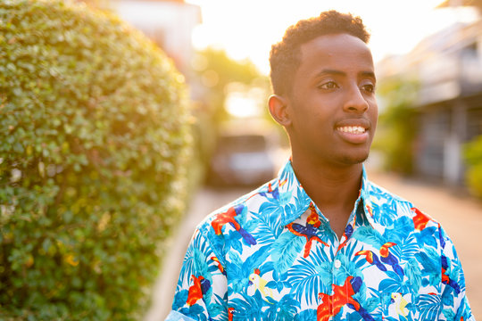 Face of happy young African tourist man thinking outdoors
