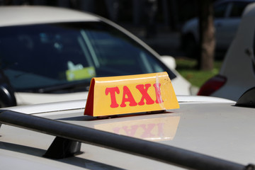 Taxi light sign or cab sign in yellow color with red text on the car roof at the street blurred background